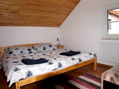 ubytování v prvním apartmánu - dřevěná postel s bílým povlečením