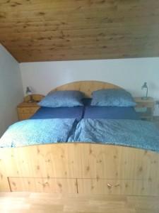 v druhém pokoji je dřevěná postel s modrým povlečením
